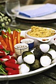 Raw vegetable platter with boiled quails' eggs and dip