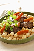 Braised pork cheeks with white beans and carrots