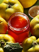 A jar of quince jelly surrounded by quinces