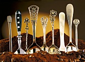 Several different spoons standing in ground coffee