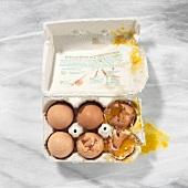 Drei ganze und drei zerbrochene Eier in der Schachtel