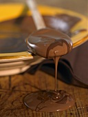 Melted chocolate running from a wooden spoon