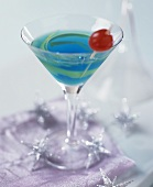 Blue Curacao cocktail with lemon peel and cherry