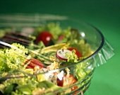 Mixed salad in a glass bowl covered with clingfilm