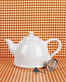 White teapot and tea strainer
