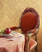 Table with pomegranate and grapes on plate, chair