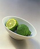 Two kaffir limes in a small bowl