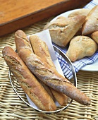 Baguettes in bread basket and plate of bread rolls