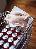 Cola tins in a shopping trolley with a raw chicken