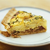 A slice of potato tart with duck confit