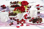 Two pieces of cherry cake on table with roses in vases