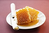 Two pieces of honeycomb with knife on a plate