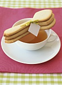 A cup of tea with three baked spoon-shaped biscuits