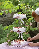 Woman decorating chocolate mousse cake on tiered stand