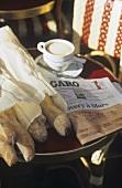Frische Baguettes & Cappucchino auf einem Tisch mit Zeitung