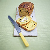 Raisin bread and slices, one buttered