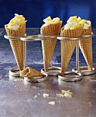 Pineapple ice cream, pineapple pieces & grated coconut in 4 waffle cones