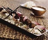 Fleischspiess auf gewürztem Reis mit Pinienkernen
