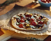 Pizza topped with merguez (sausage) and black olives