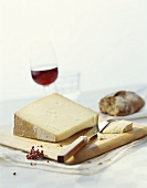 A piece of hard cheese with knife on a wooden board, wine