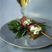 Fish kebab on pepper salad with beetroot leaves