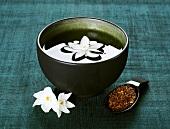 Narcissus flower in bowl of water, tea & flowers beside it