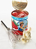 Tinned tomatoes with whisk and garlic