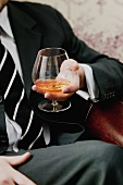 Man holding a glass of cognac in his hand