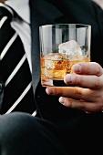 Ein Glas Cognac mit Eiswürfeln