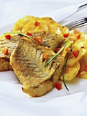 Fried fish fillet with diced peppers and potato gratin