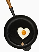 Heart-shaped fried egg in frying pan