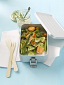 Pasta salad with salmon and green asparagus in lunch box