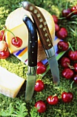 Goat's cheese, two knives and cherries