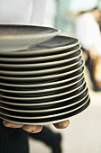 Waiter holding a pile of plates in his hands