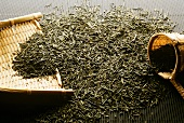 Green tea, dried leaves with bamboo tea strainer