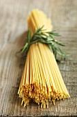 Ein Bund Spaghetti mit Rosmarinzweig umwickelt