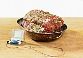 Prime rib in roasting dish with meat thermometer