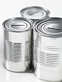 Three empty food tins with slots in the top