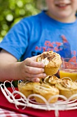 Small boy reaching for apple and cinnamon muffins