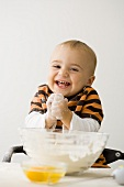 Small boy with floury hands in front of bowl of flour