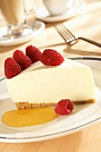 A slice of cheesecake with raspberries and fruit sauce