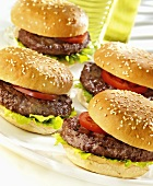 Four hamburgers with tomato and lettuce leaf