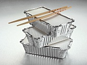 Three aluminium take-away food containers and chopsticks