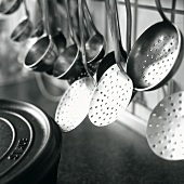 Ladles and skimmers hanging on a rack