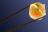 Fish gunkan maki in chopsticks