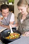 Junge Frau rührt Gemüse im Wok, Mann hält ein Glas Wein