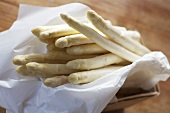 White asparagus with greaseproof paper in small basket
