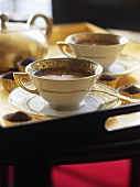 Two cups of tea with chocolate truffles on a tray