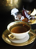 A cup of tea with chocolate truffles in background