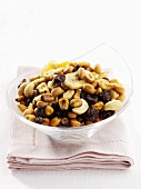 Trail mix with dried fruit, nuts, dried banana in glass bowl